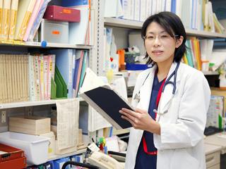 本棚の前に立つ竹中先生